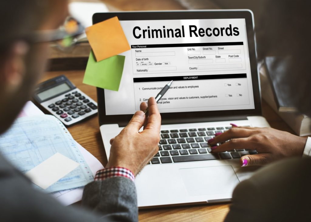 """Criminal record: 2 people in front of a laptop sayng """"Criminal records"""" on the screen"""