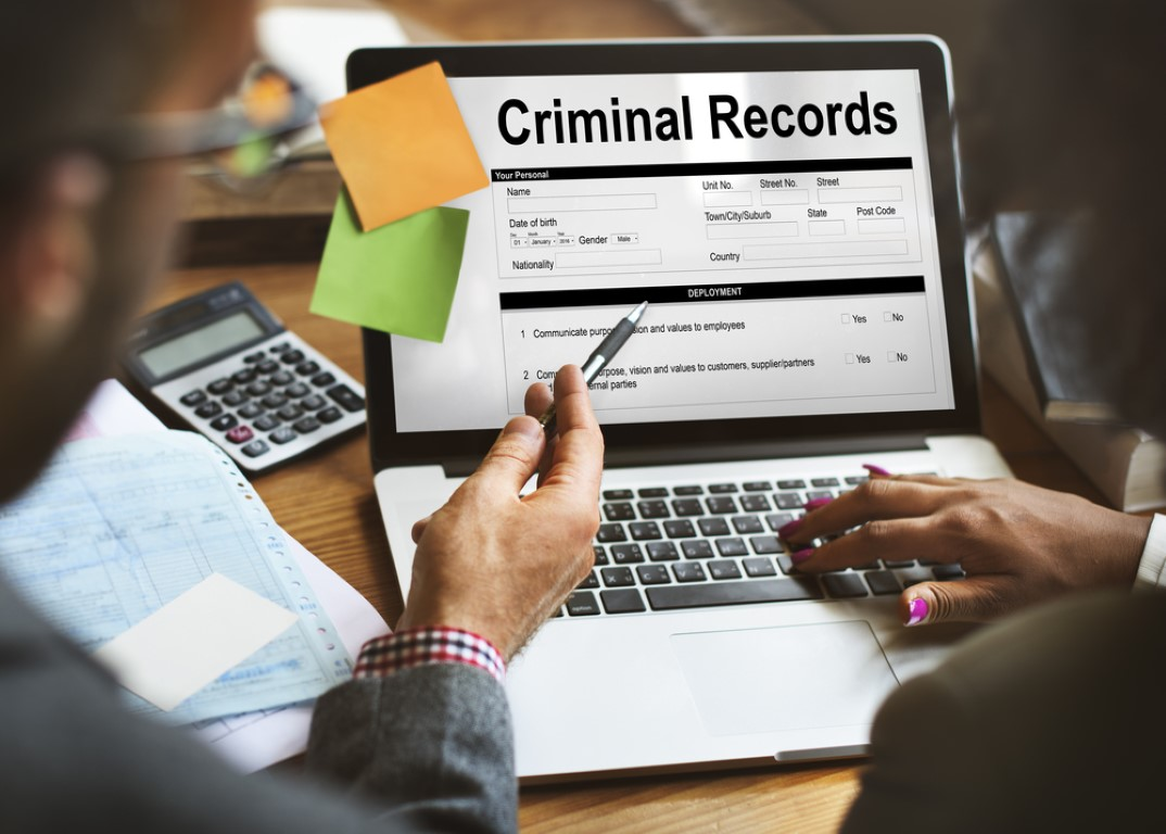 "Criminal record: 2 people in front of a laptop sayng ""Criminal records"" on the screen"